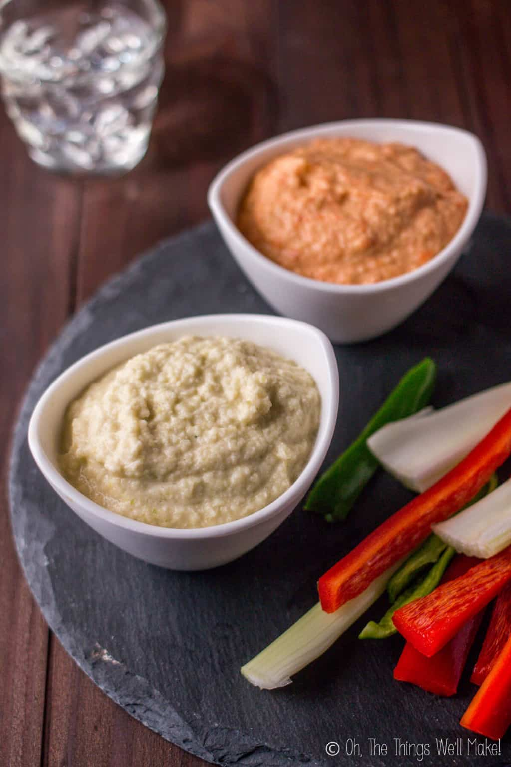 Two bowls of zucchini hummus on a black slate platter with cut veggies. Bottom bowl is filled with plain zucchini hummus while the bowl on top is orange zucchini hummus flavored with roasted red peppers.
