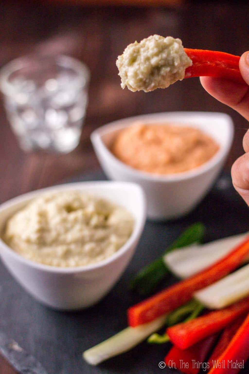 Close-up of a hand holding a red pepper strip topped with zucchini hummus with two bowls of zucchini hummus in the background.