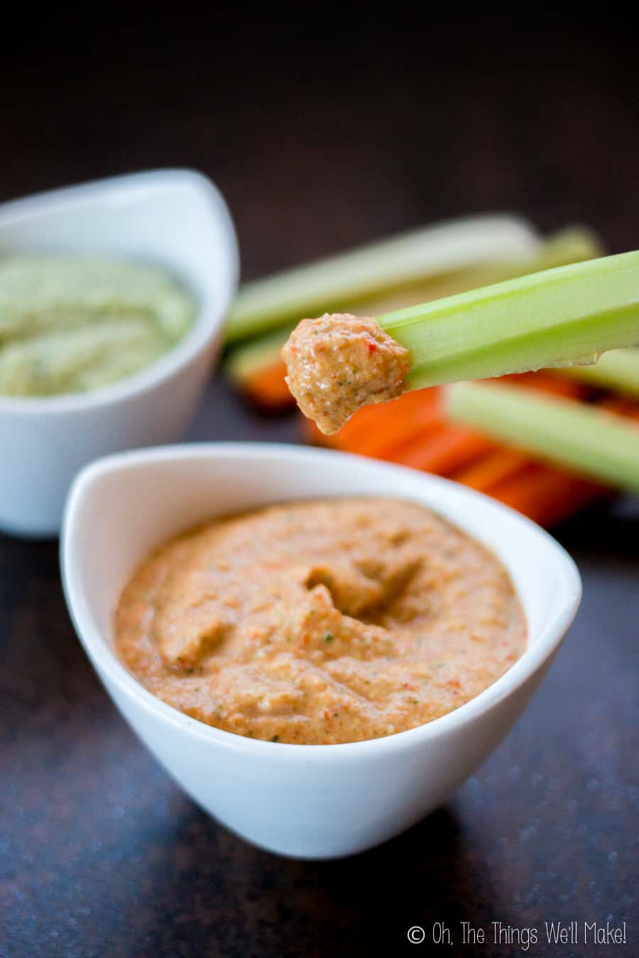 Dipping celery into roasted red pepper zucchini hummus