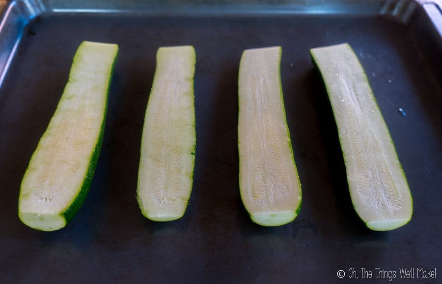 Zucchini sliced in half lengthwise on a baking tray