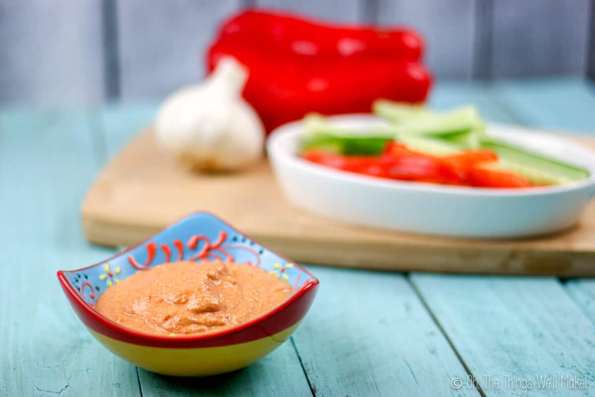 Close up of a bowl of roasted red pepper zucchini hummus in a bowl in front of some raw cut veggies.