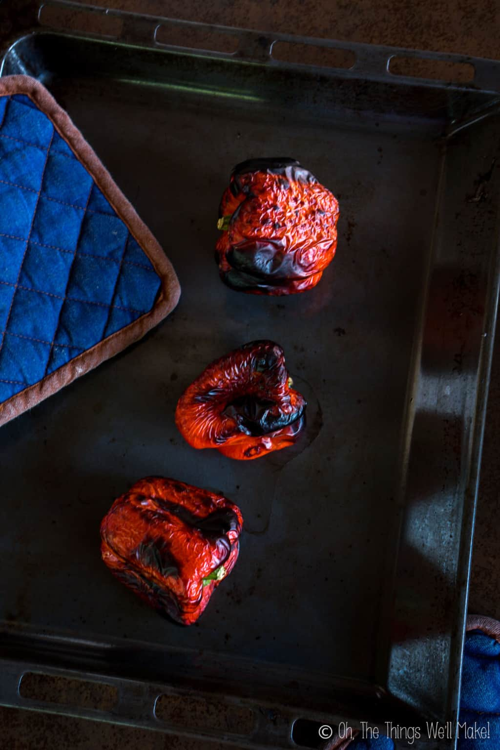 Top view of three roasted red peppers with char-broiled skin on a baking pan