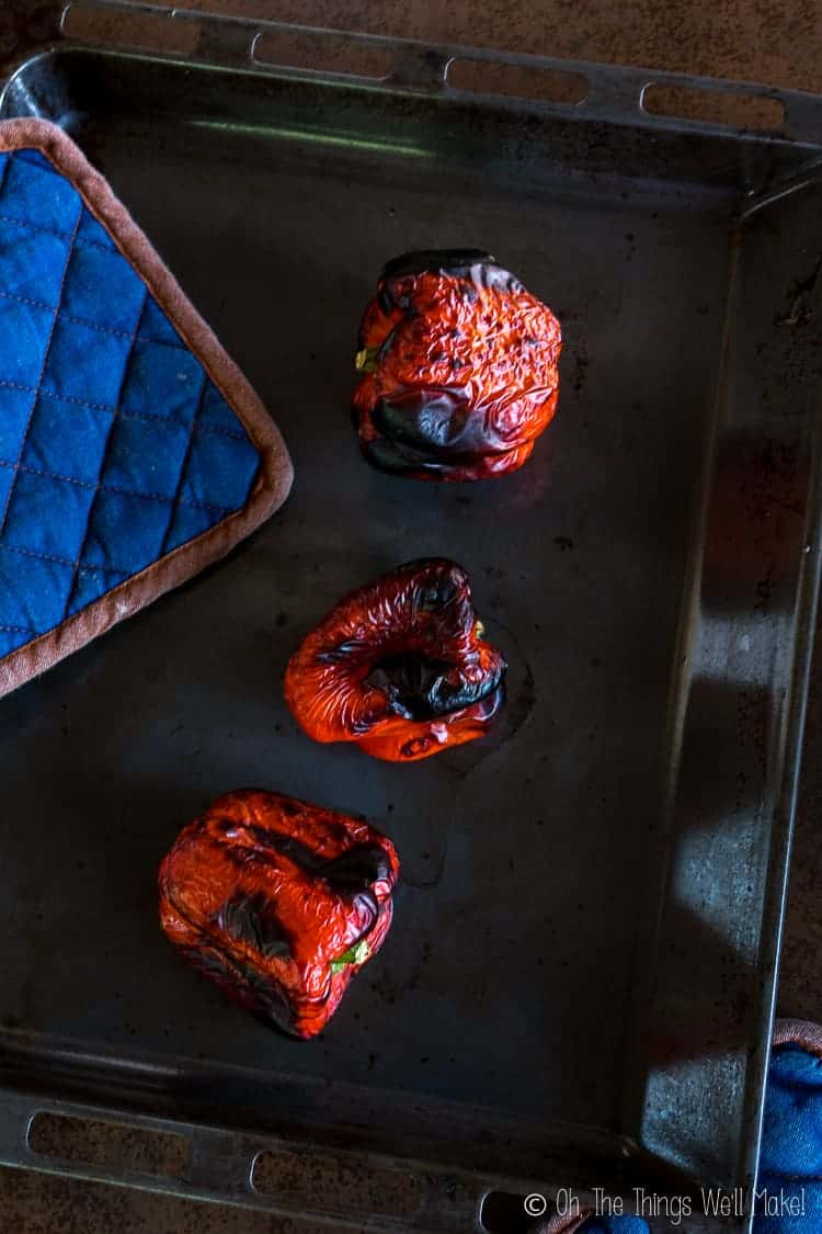 3 roasted red peppers with char-broiled skin on a baking pan