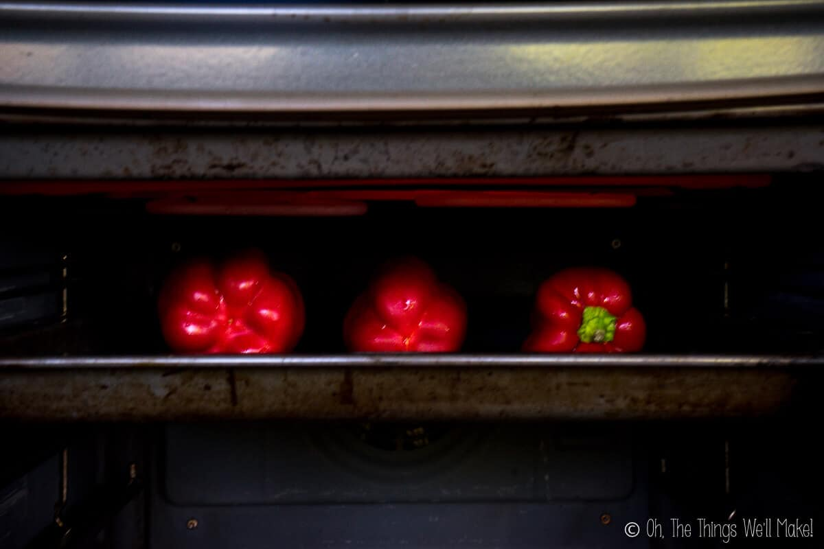 Three red peppers on a baking sheet under a broiler.