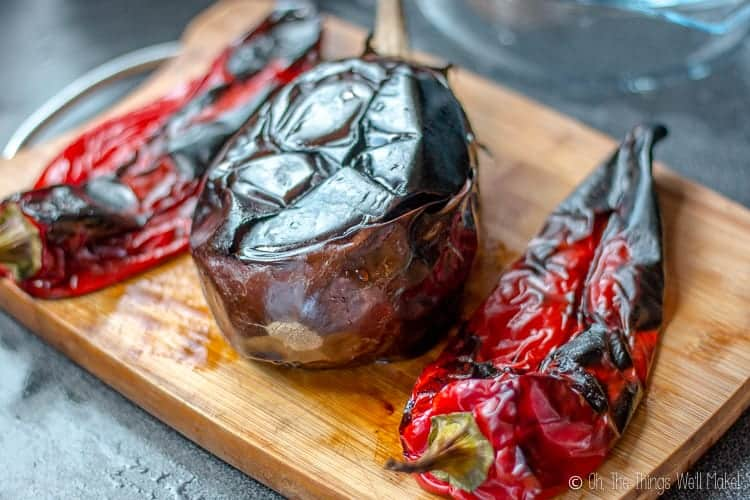 Charbroiled red Italian peppers with a charbroiled eggplant on a bamboo cutting board.