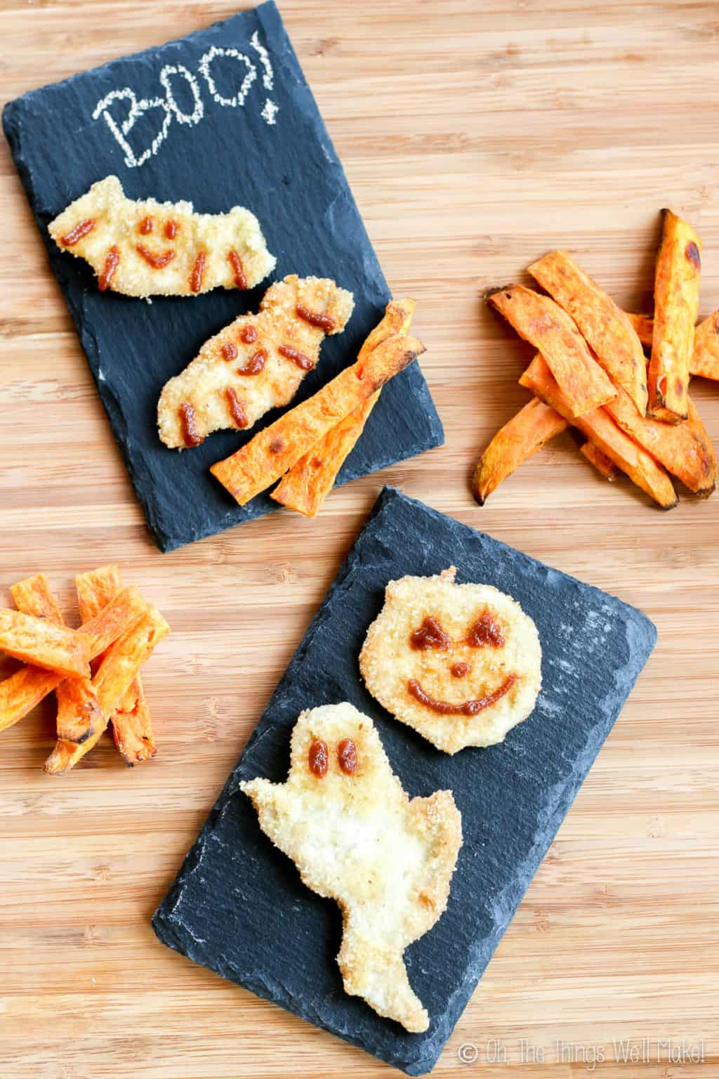 Halloween chicken nuggets placed on black rectangular plates, shaped like ghosts, pumpkins, and bats, and decorated with BBQ sauce. There are several pieces of sweet potato fries around the plates.