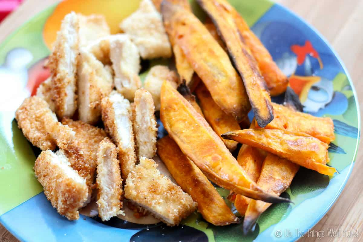 Close up of sliced homemade breaded chicken with baked sweet potato fries on the side.