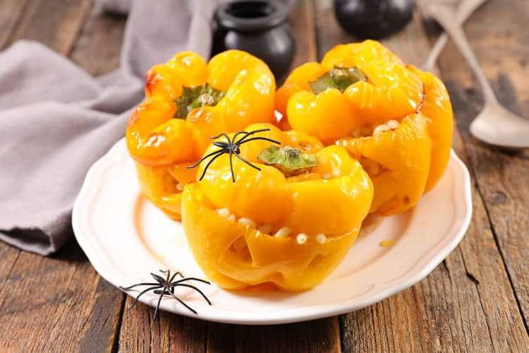 A plate of 3 yellow bell peppers that have been carved like a jack-o-lantern and filled with pasta decorated with plastic spiders.