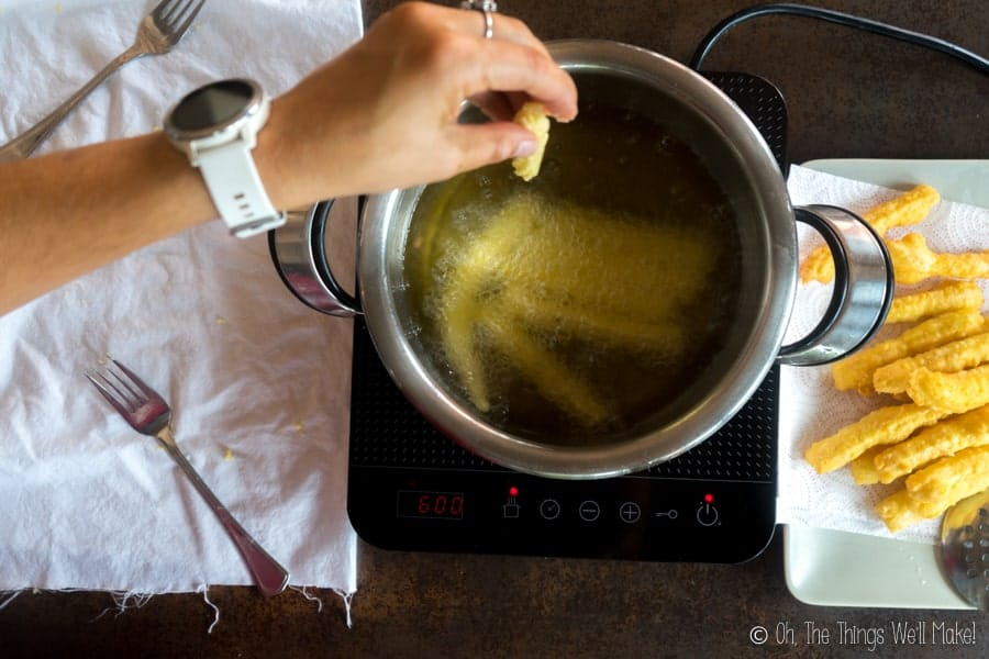 Adding the churros dough to the hot olive oil