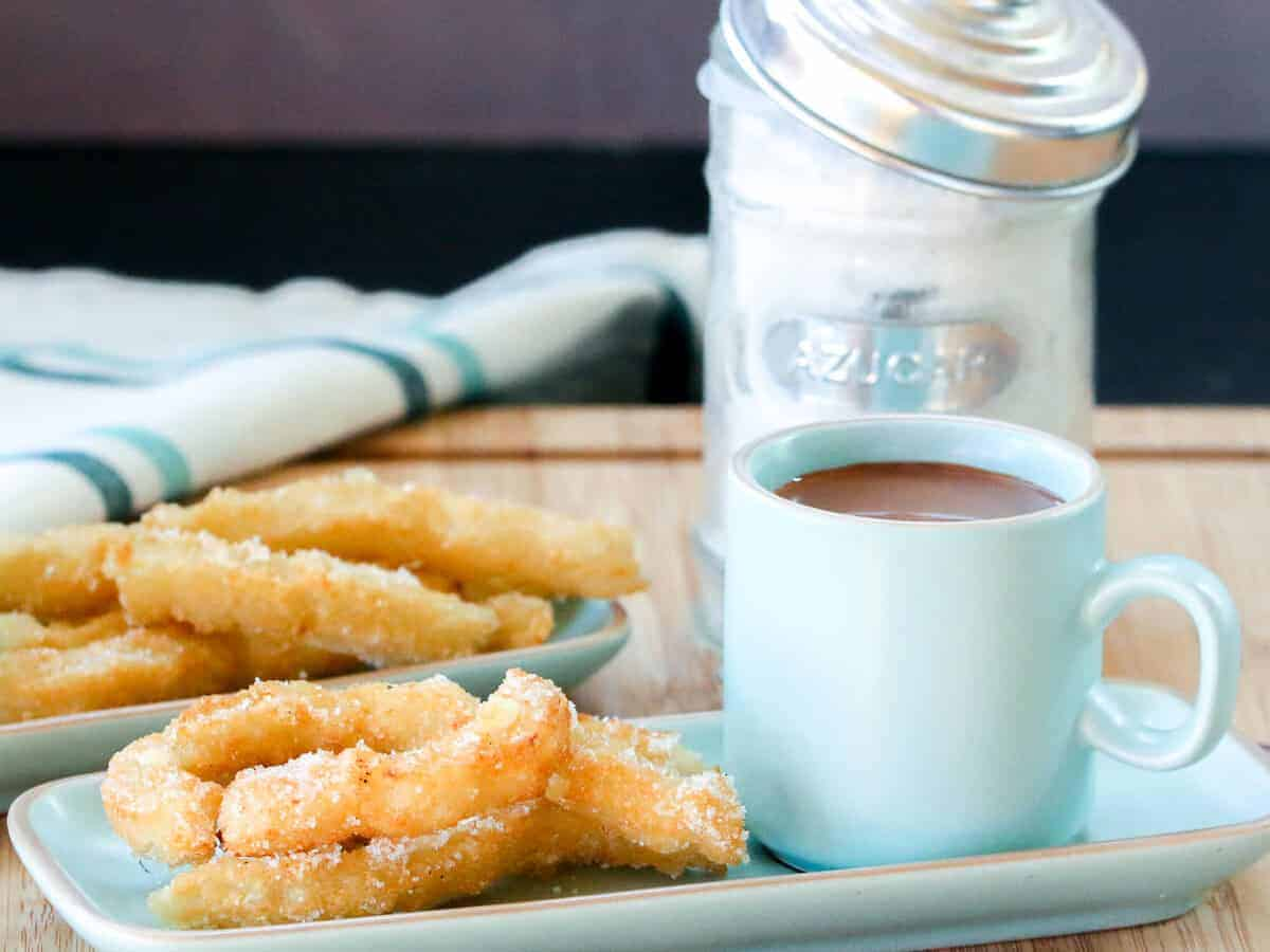 Overhead view of two plates of churros sprinkled with sugar with a cup filled with Spanish hot chocolate next to it.