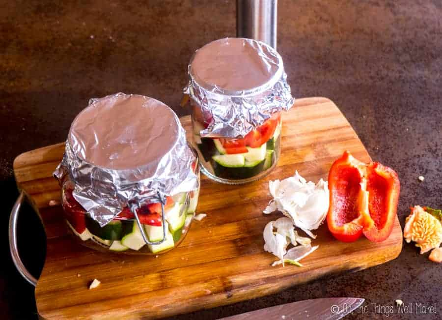 Jars filled with vegetables and salmon, covered with foil.