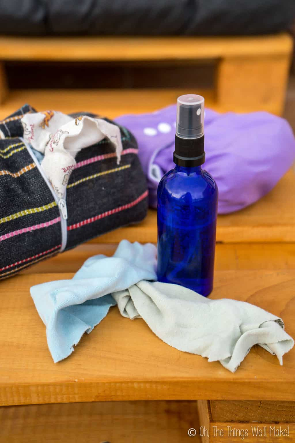 A small blue glass bottle with a DIY baby wipe solution next to a black with colorful stripes fabric dispenser filled with homemade cloth wipes and a purple cloth diaper at the back.