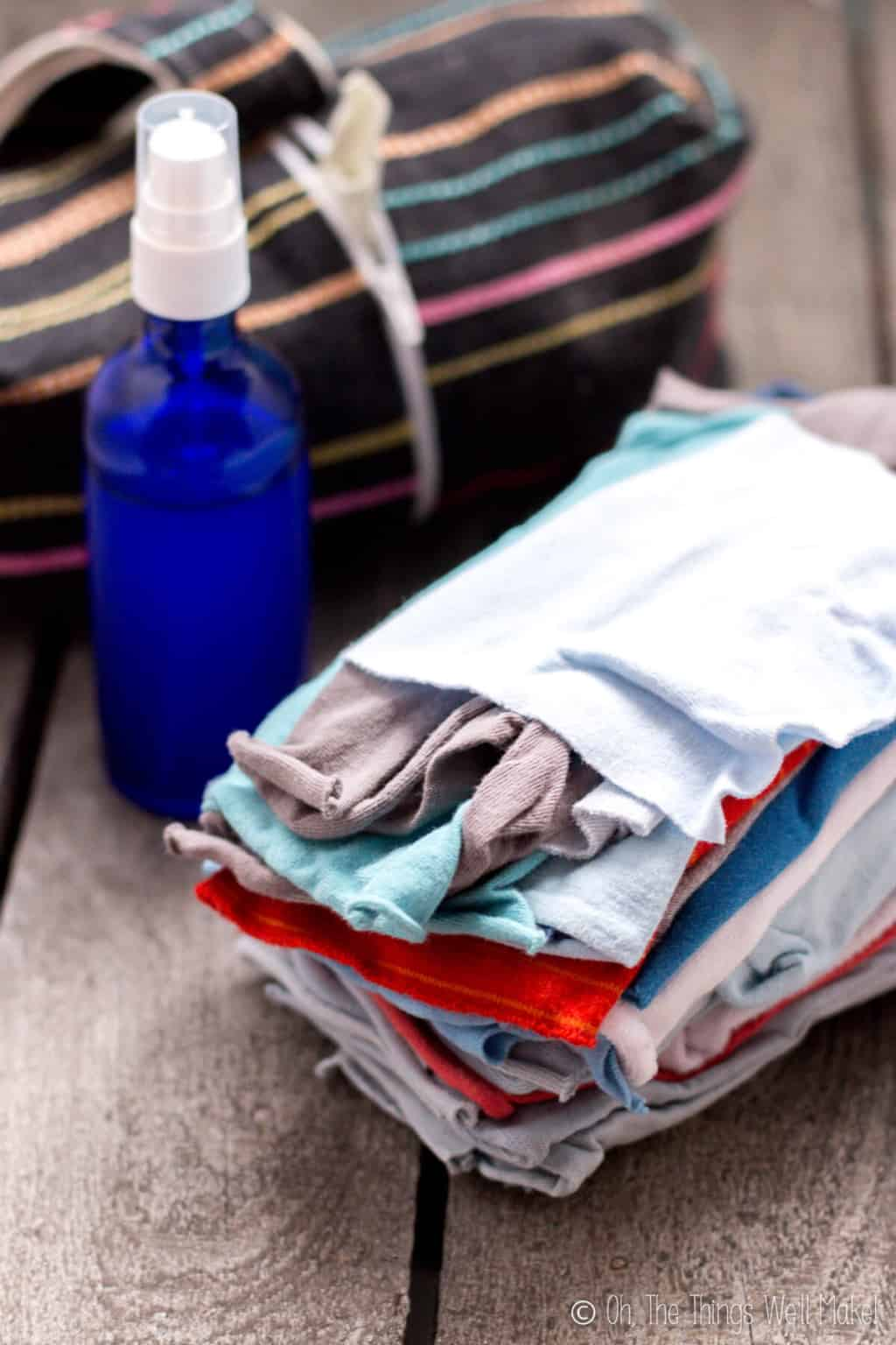 A stack of colorful homemade cloth wipes in front of a blue glass bottle filled with wipe solution.