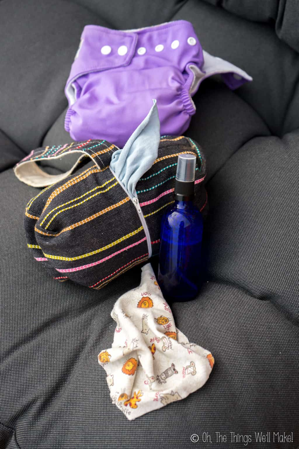 A small blue glass bottle with baby wipe solution, a black with stripes design cloth wipes dispenser, and a purple cloth diaper.