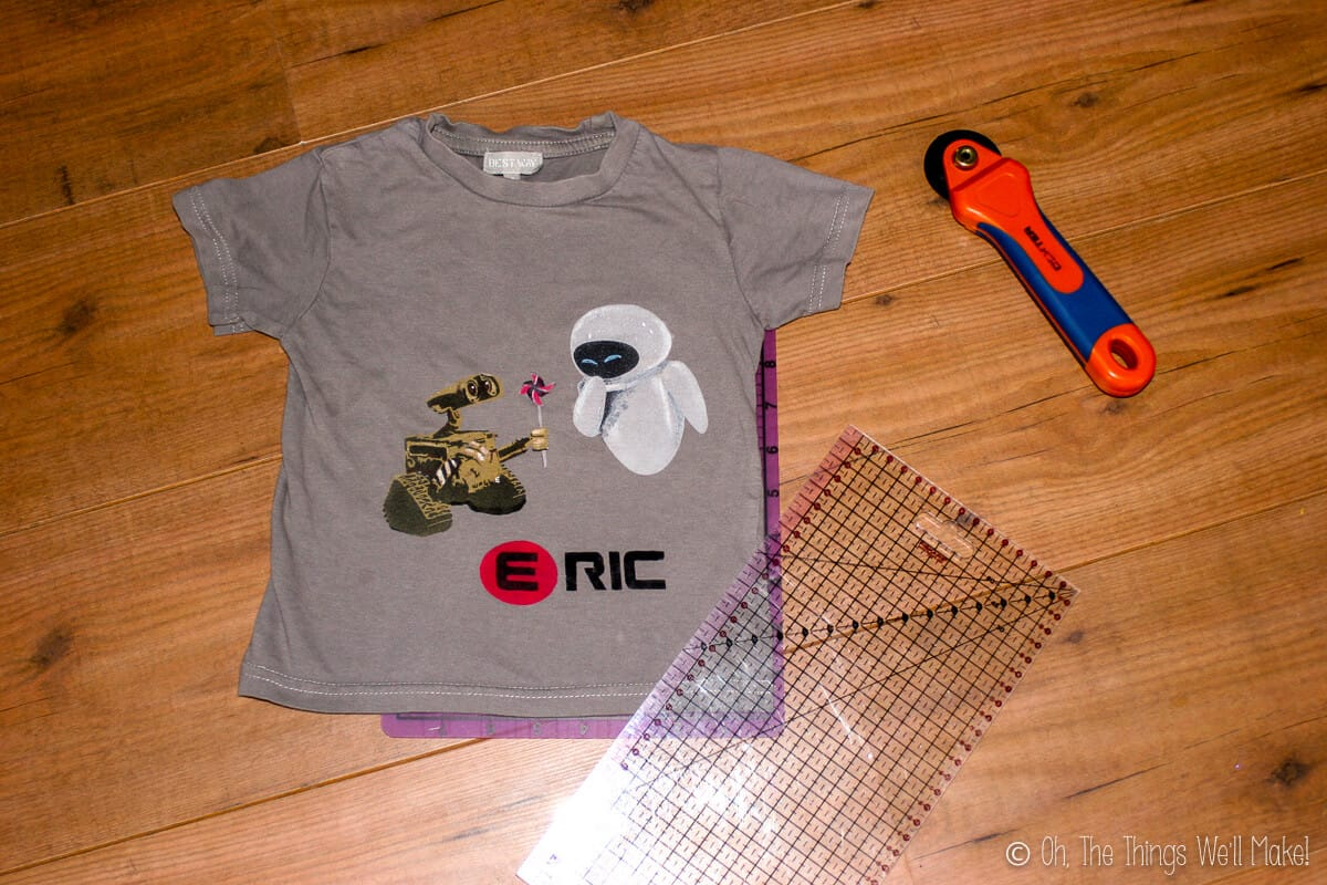 Overhead view of grey Wall-E t-shirt, a rotary cutter, and a plastic ruler mat, laid on a wood surface.