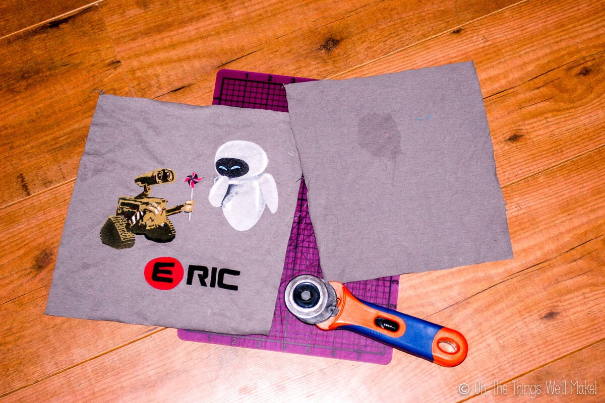 Overhead view of two squares of grey fabric cut from a t-shirt, laid on a purple cutting mat with a rotary cutter on the bottom. One square has a Wall-E design on it and one is plain.