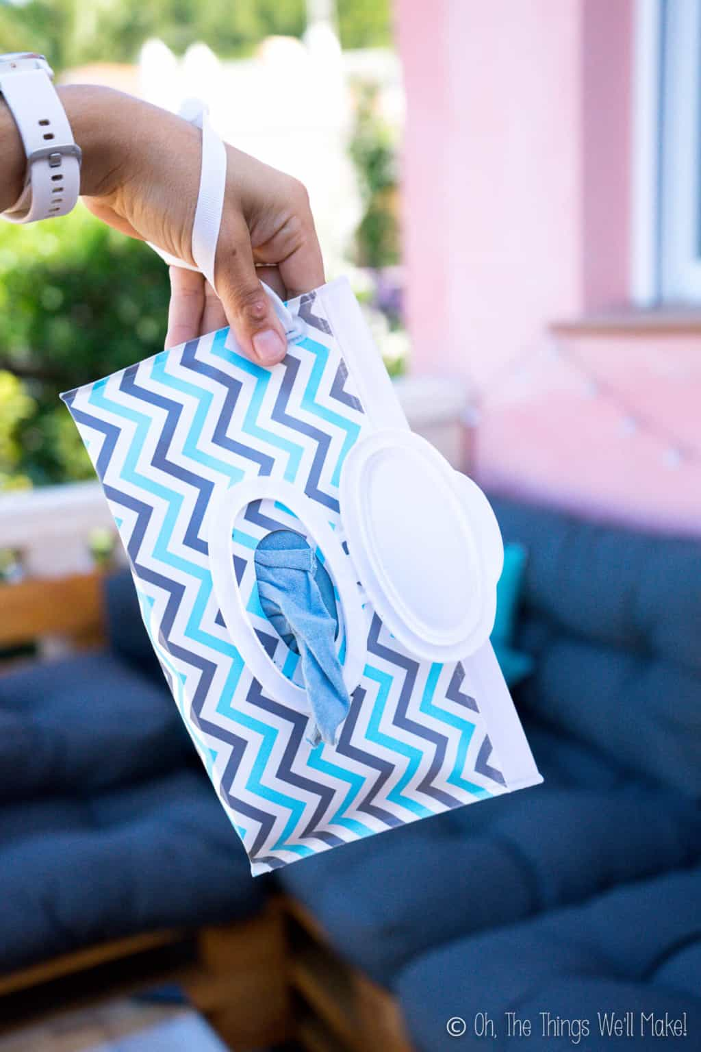A hand holding onto a chevron printed plastic pouch wipes dispenser open with a cloth wipe peaking out.