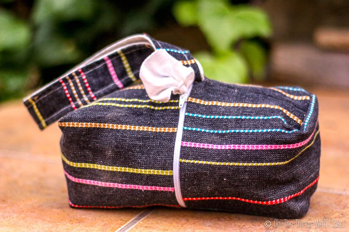 A rectangular black with colorful stripes fabric bag that is actually a baby cloth wipes dispenser.