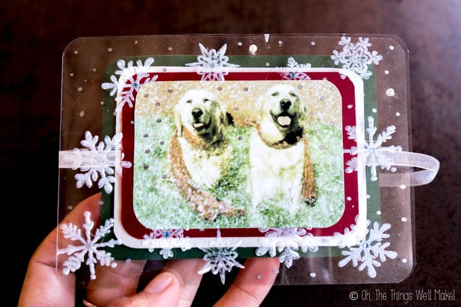 The front of a transparent acetate Christmas card decorated with white snowflakes