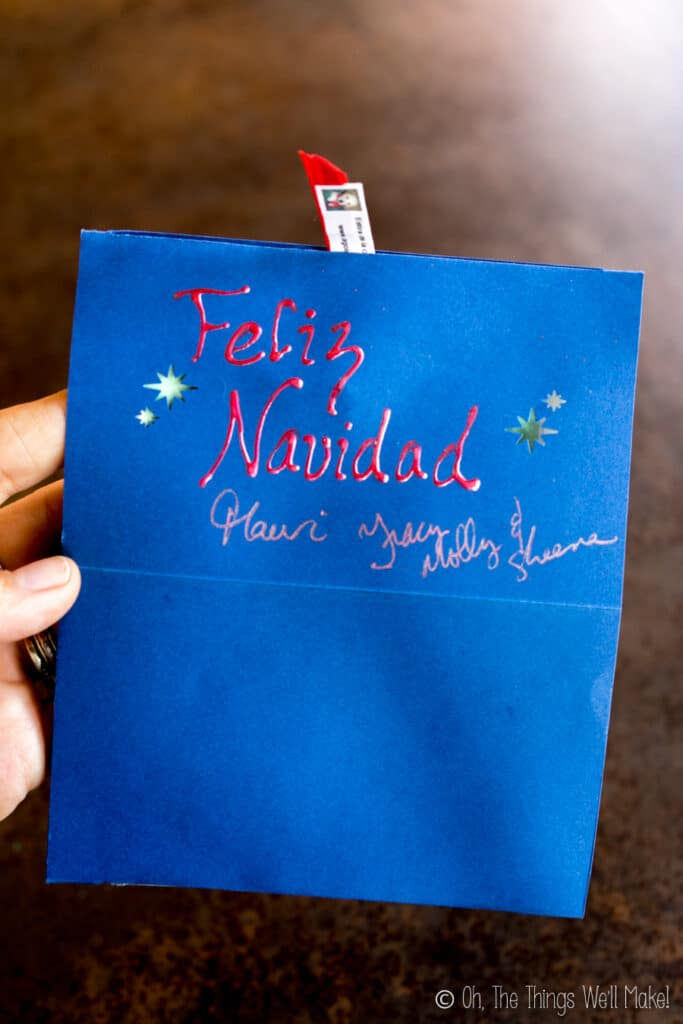 "A handmade card with ""Feliz Navidad"" written on the front and a tab to pull on top."