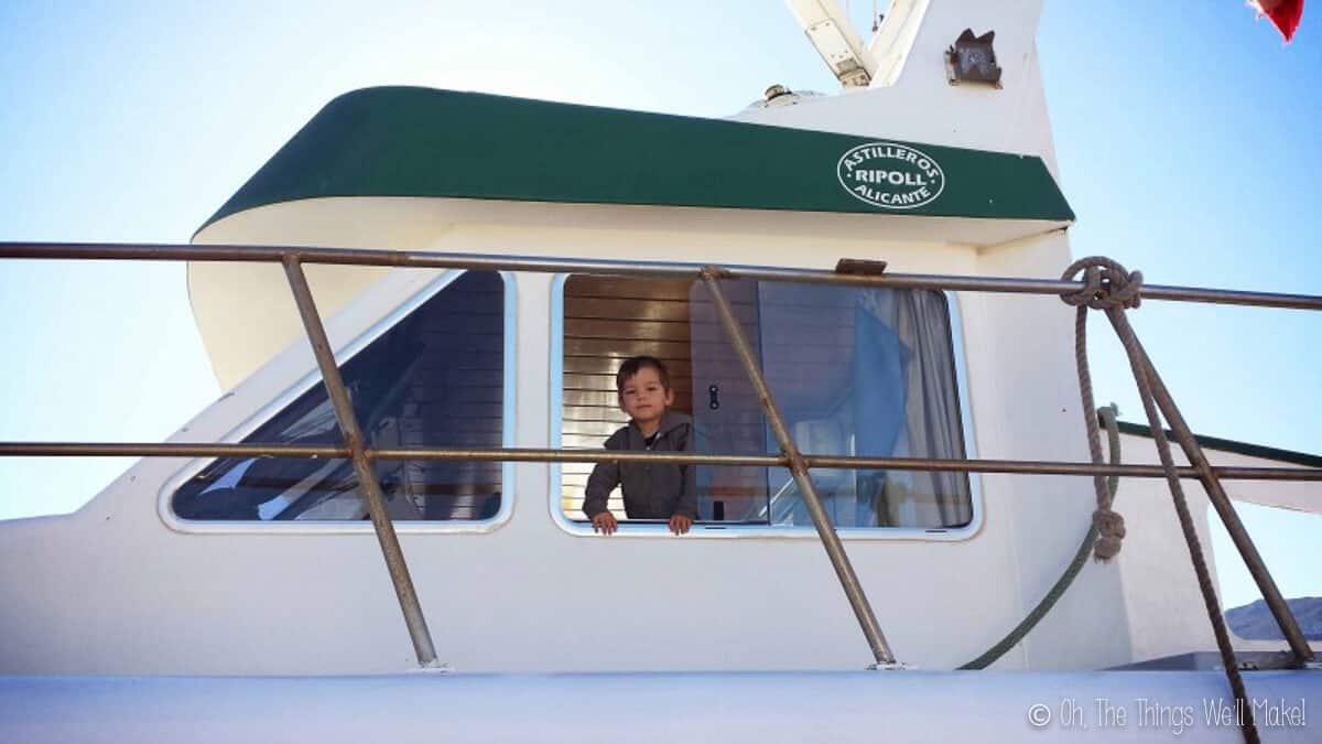 A young boy looking out the window of a white fishing boat.