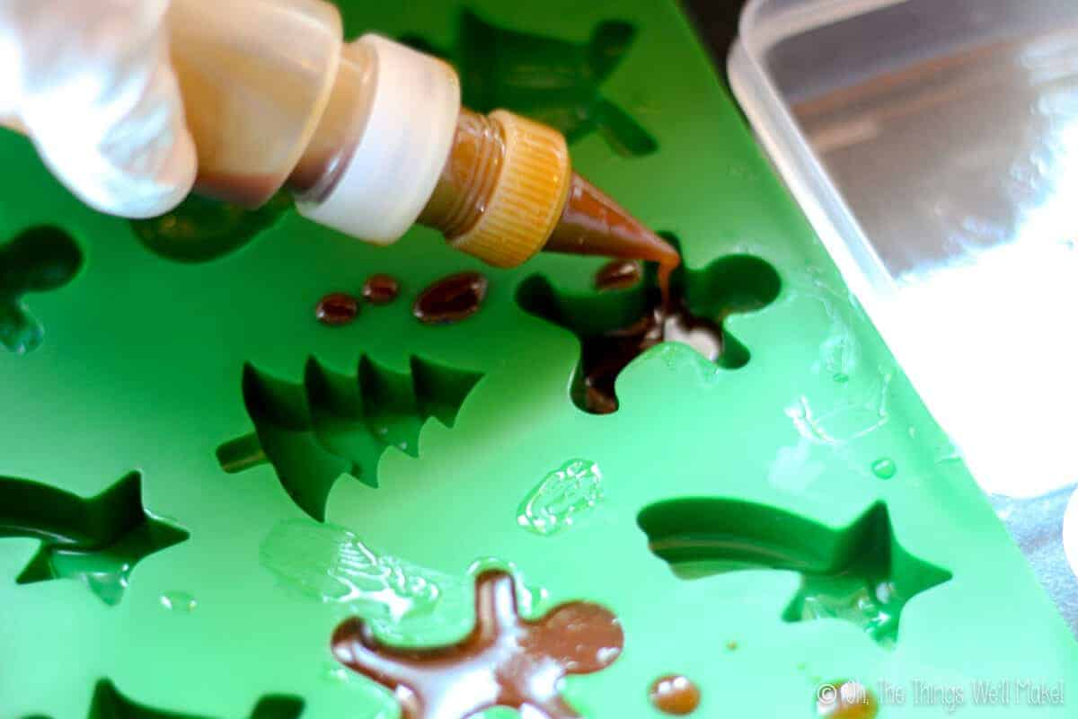 Piping the gingerbread soap mixture into silicone candy molds shaped like gingerbread men