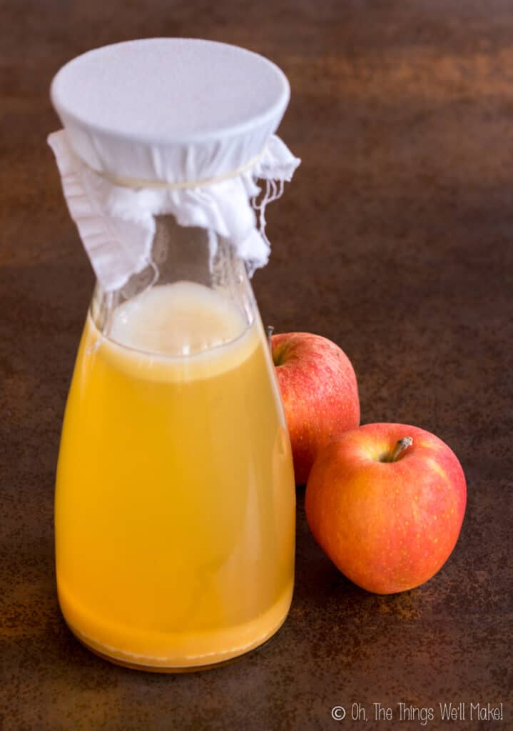 A carafe of homemade apple cider vinegar with 2 red apples behind it.