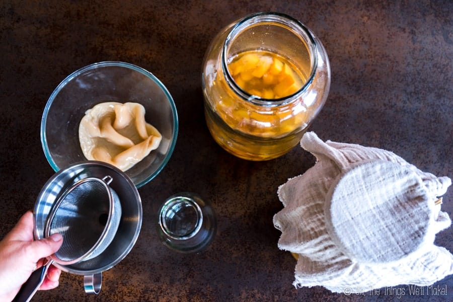 homemade vinegar in a jar with the mother in a bowl and a funnel and strainer being placed on a bottle to strain the vinegar.