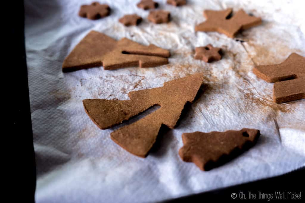 A baking sheet with several homemade cinnamon ornaments one it. One has edges that have curled upwards.