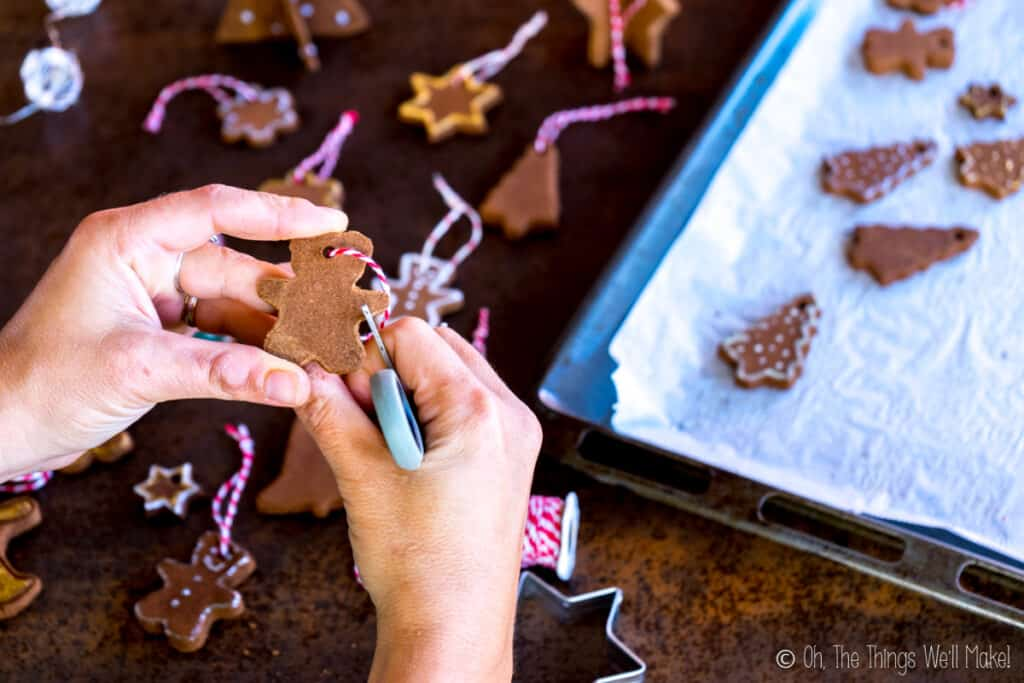 Scrapiing the edges of cinnamon ornaments with the edge of a pair of scissors