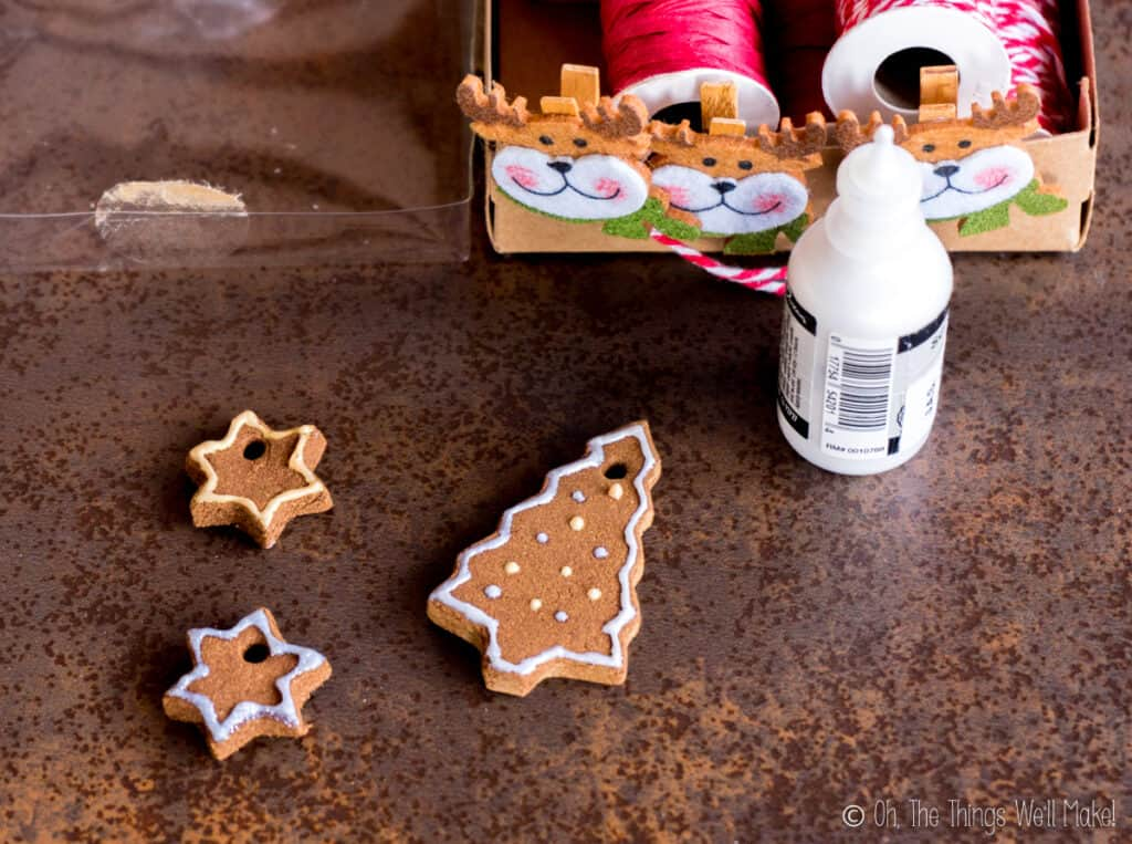 Overhead view of homemade cinnamon ornaments painted with dimensional paints next to a bottle of paint
