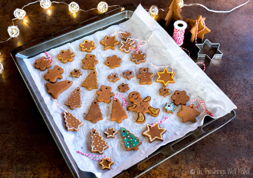 Overhead view of a baking sheet filled with many cinnamon ornaments, some which have been oainted