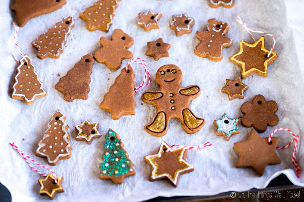 Closeup of a baking sheet filled with many cinnamon ornaments, some which have been oainted