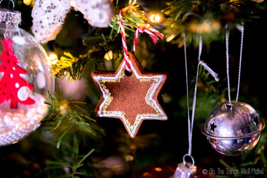 Closeup of a star shaped cinnamon ornament hanging on a Christmas tree