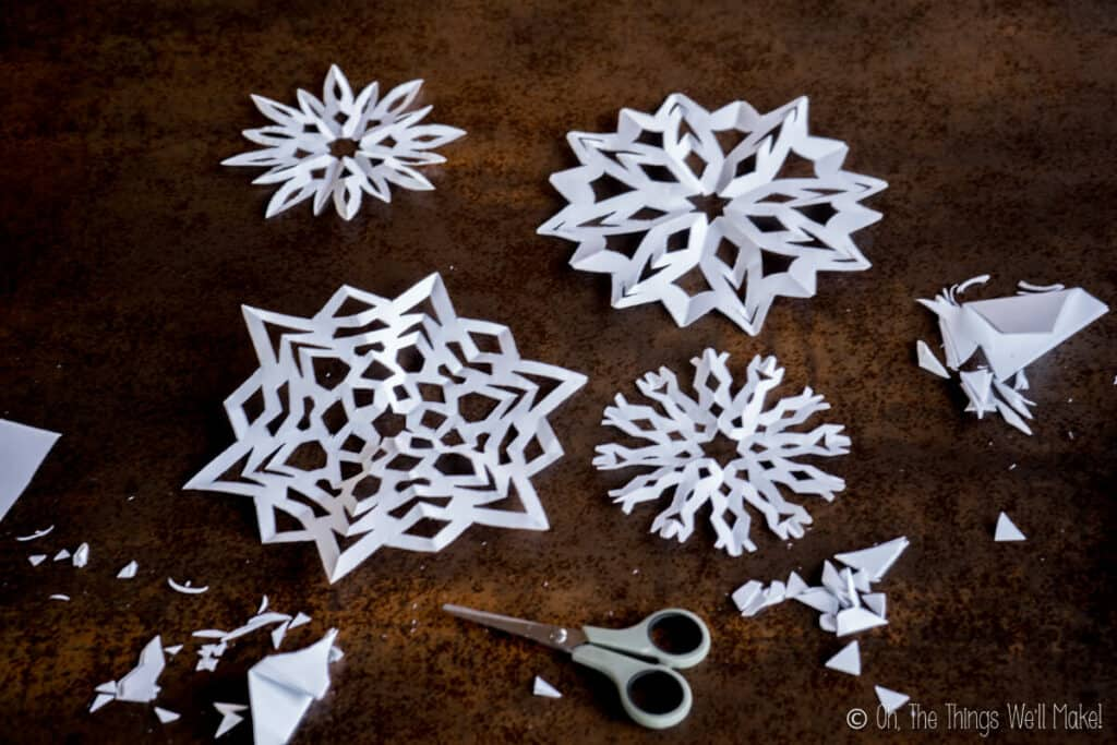 Multiple paper snowflakes that have been cut out of paper