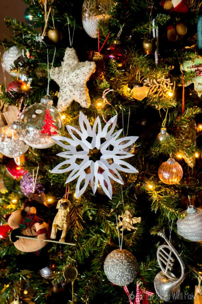 A paper snowflake hanging on a Christmas tree with other ornaments