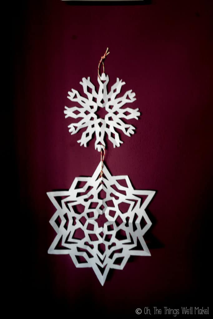 Two paper snowflakes strung together and hanging from a wall