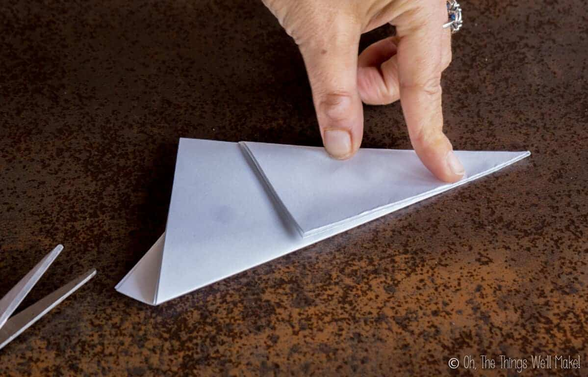 Folding down the other third of the rectangular piece of paper, forming a triangular shape