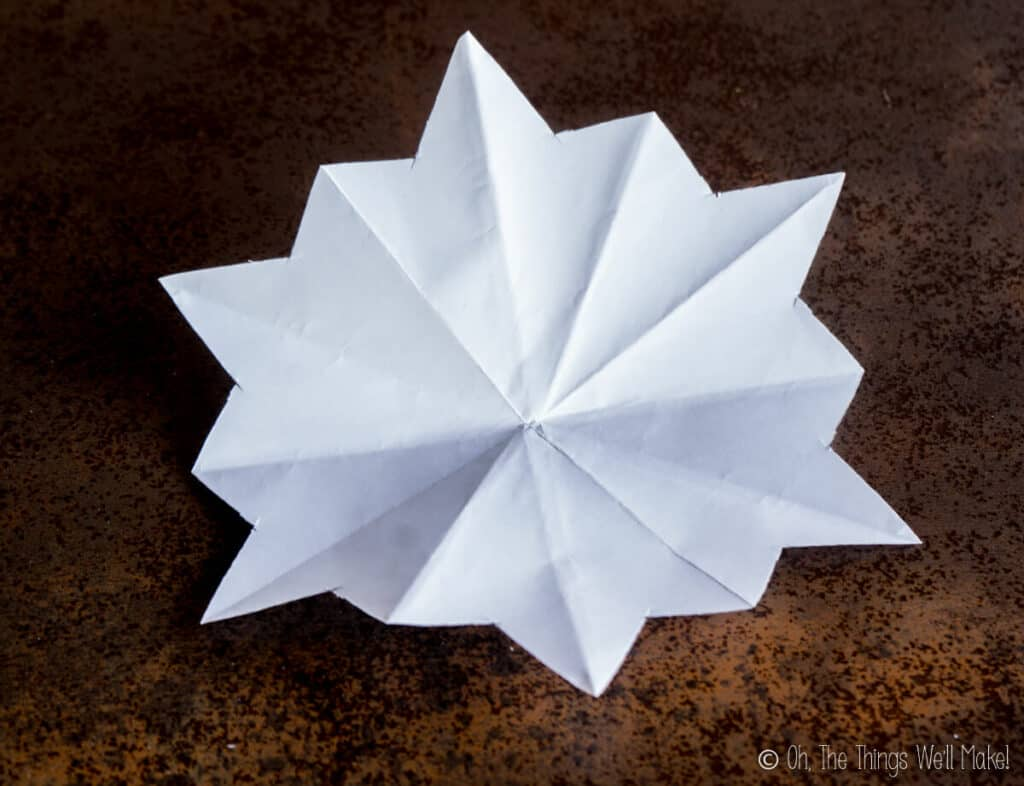 A piece of paper that has been folded and cut and ready for making into a paper snowflake.
