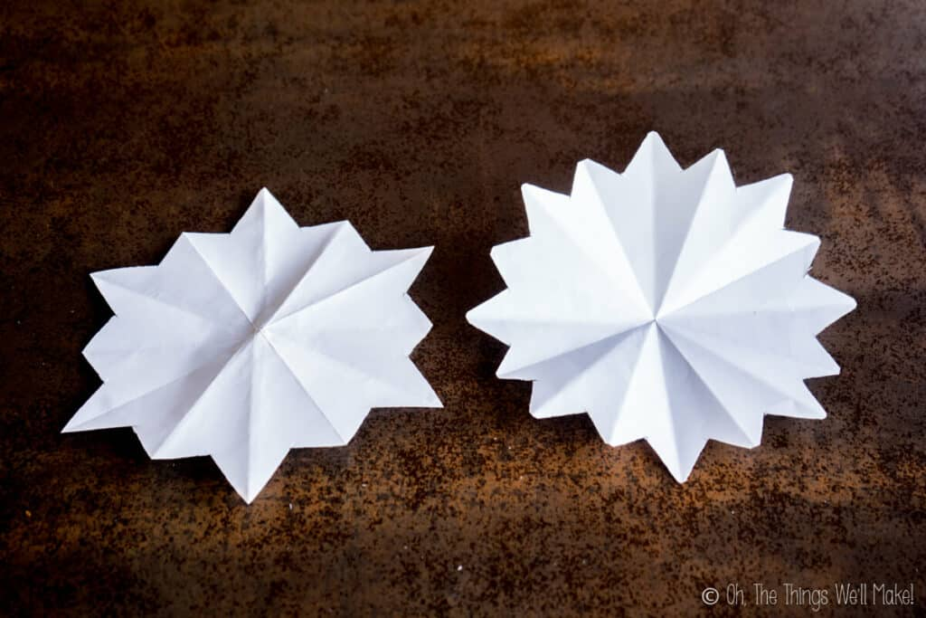 Two pieces of paper that have been folded and cut in preparation for making into paper snowflakes, the one on the left is for making a 6 pointed snowflake and the one on the right for 8 pointed snowflakes
