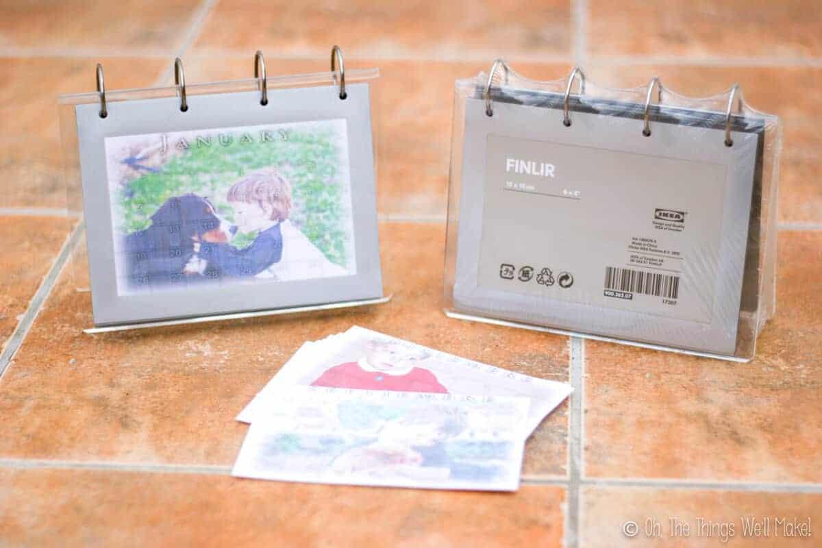 A homemade photo calendar next to an empty flip photo frame and some printed out calendar sheets.