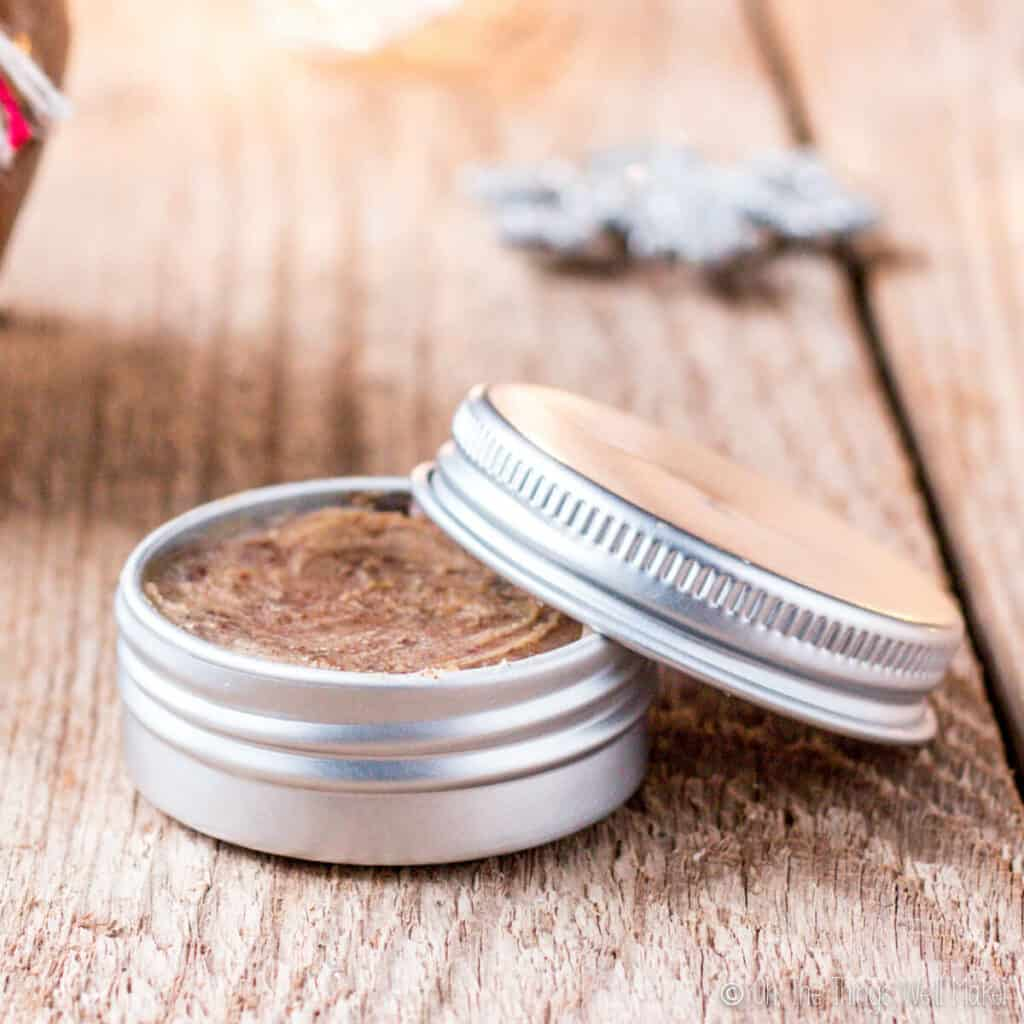 Closeup of an aluminum tin filled with a brown sugar lip scrub. The lid of the tin is resting over the side of the tin.