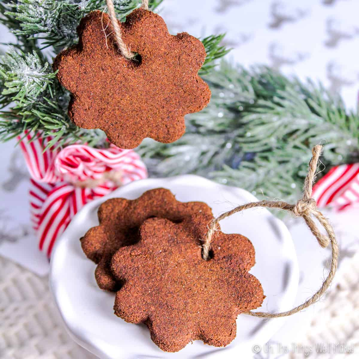 3 homemade applesauce cinnamon ornaments, one hanging from a tree and two on a white plate