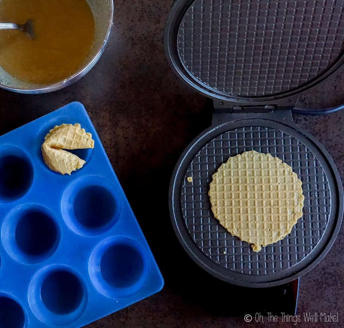 overhead view of fortune cookies being made in a pizzelle iron.