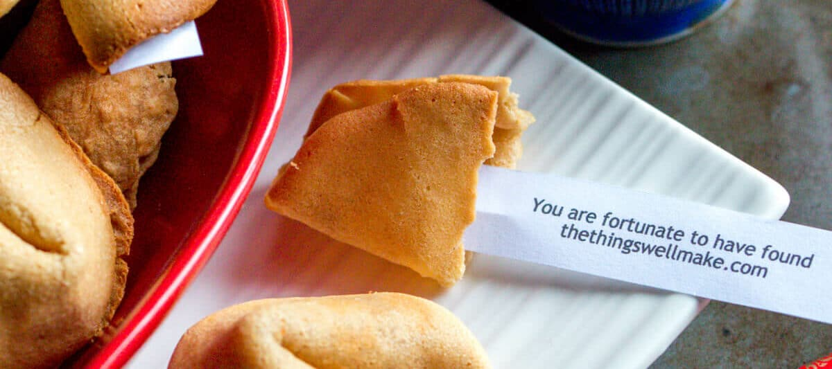 """Overhead view of several homemade fortune cookies. One has been opened to show a fortune that reads """"You are fortunate to have found thethingswellmake.com""""."""