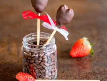 two chocolate-covered strawberry hearts in a jar next to a whole strawberry and a heart-shaped strawberry on a skewer ready for dipping in chocolate.