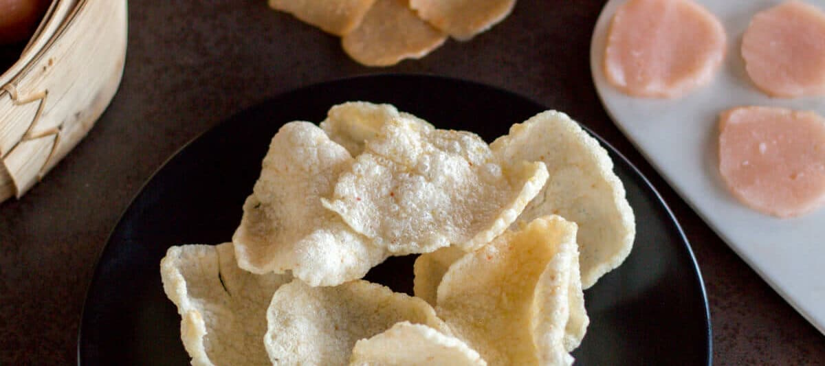 Homemade prawn crackers on a plate in front of uncooked homemade prawn crackers and a roll of prawn crackers dough.