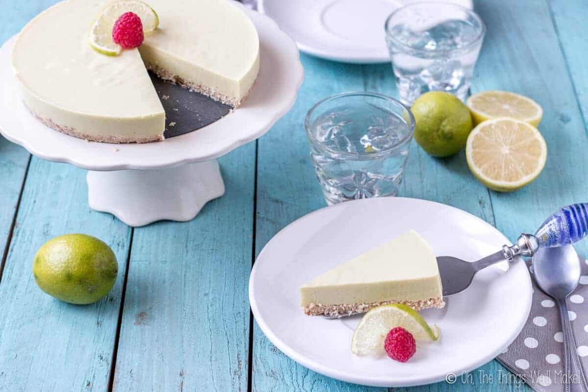 Overhead view of a homemade paleo key lime pie on a cake stand with a slice of it being placed on a white plate using a spatula.