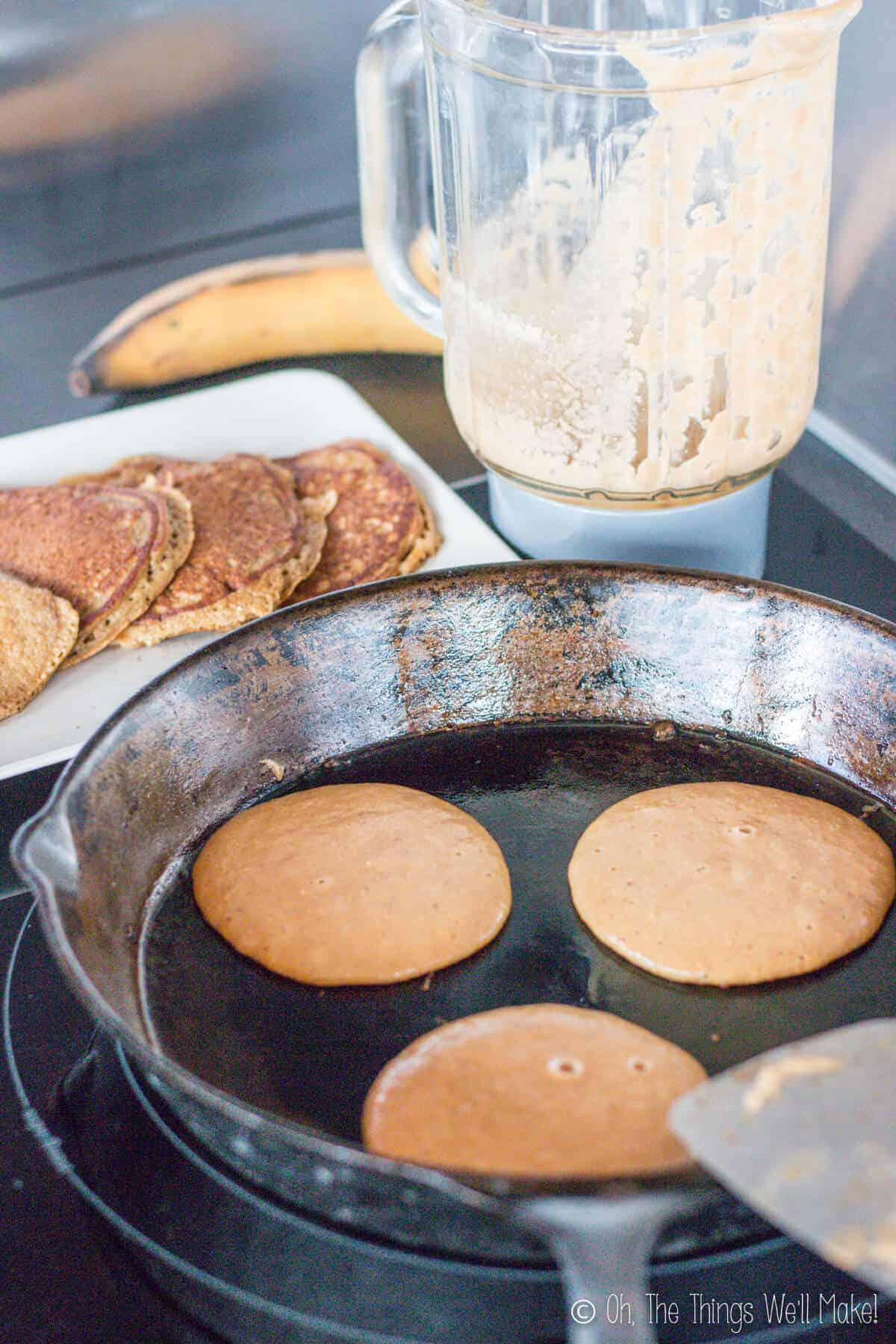Frying 3 paleo pancakes on a cast iron skillet in front of some already made healthy pancakes.