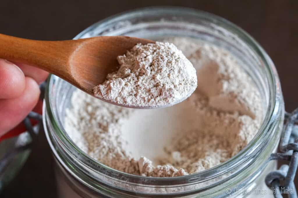 A wooden spoon full of bentonite clay powder held over a glass jar of bentonite clay.